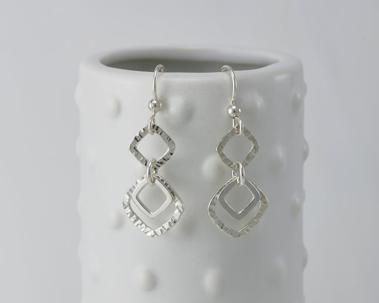 Silver polished hammered squares earrings on dotted vase