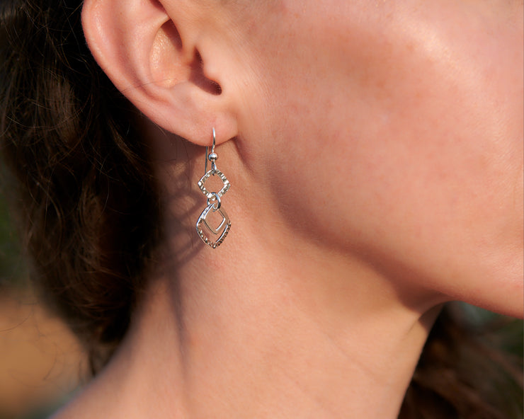 close-up of woman wearing silver hammered squares earrings