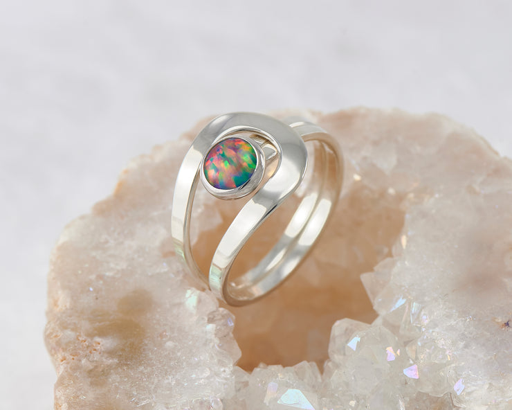 fire opal silver wrap ring resting in quartz
