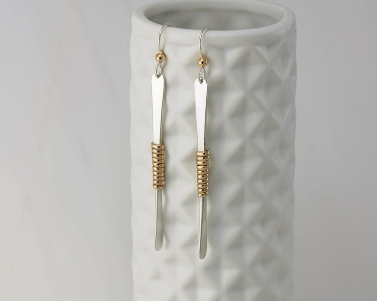 gold bar earrings on geometric vase