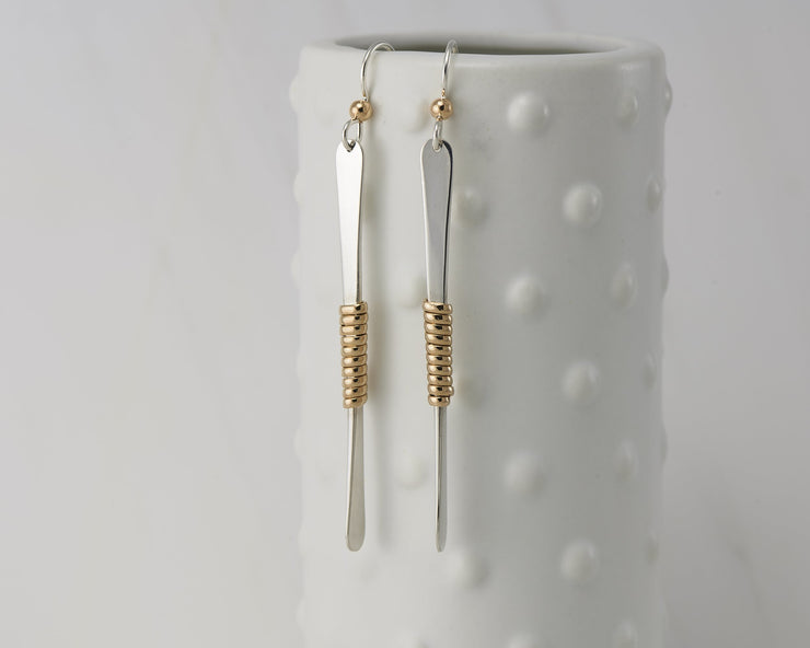 gold bar earrings on dotted vase