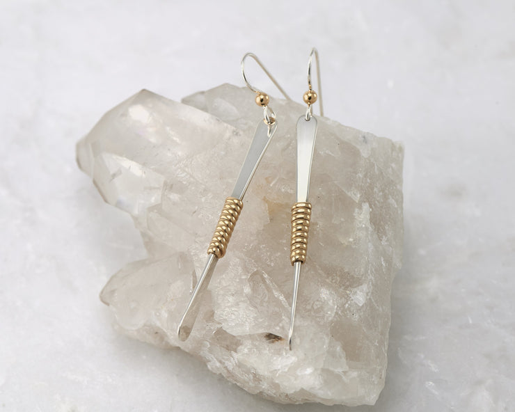 gold bar earrings on white crystal