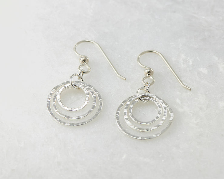 Silver polished hammered hoop earrings on white marble