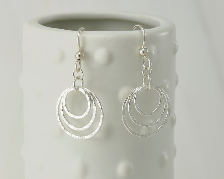 Silver polished hammered hoop earrings on dotted vase