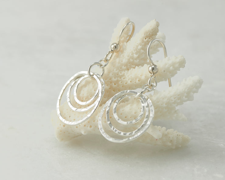 Silver hammered hoop earrings on coral