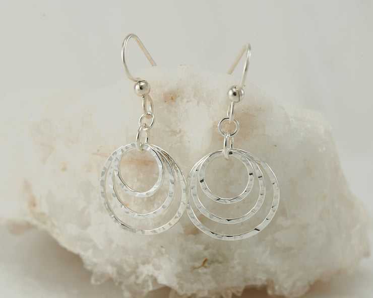 Silver hammered hoop earrings on white rock