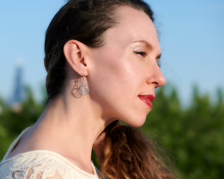 Woman wearing silver hammered hoop earrings