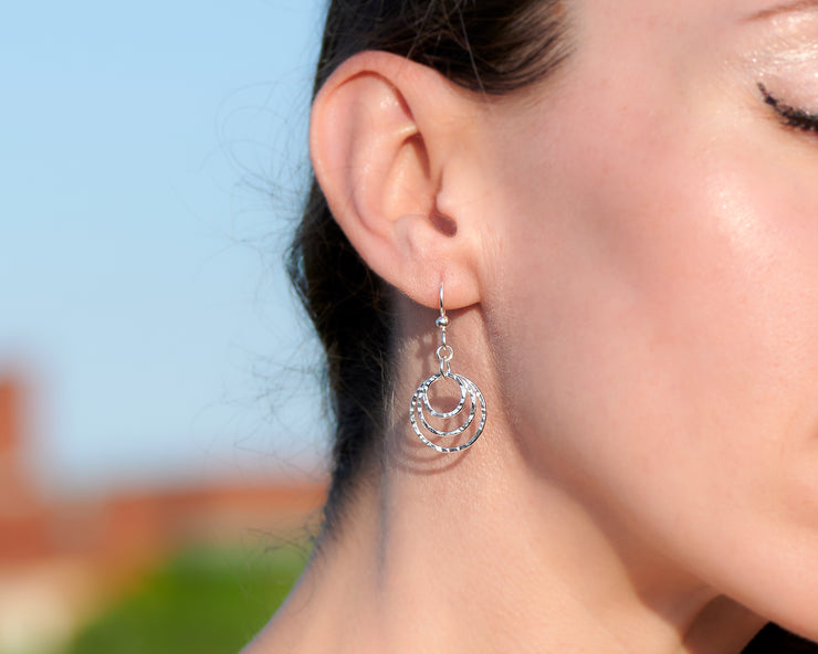 close up of woman wearing silver hammered hoop earrings