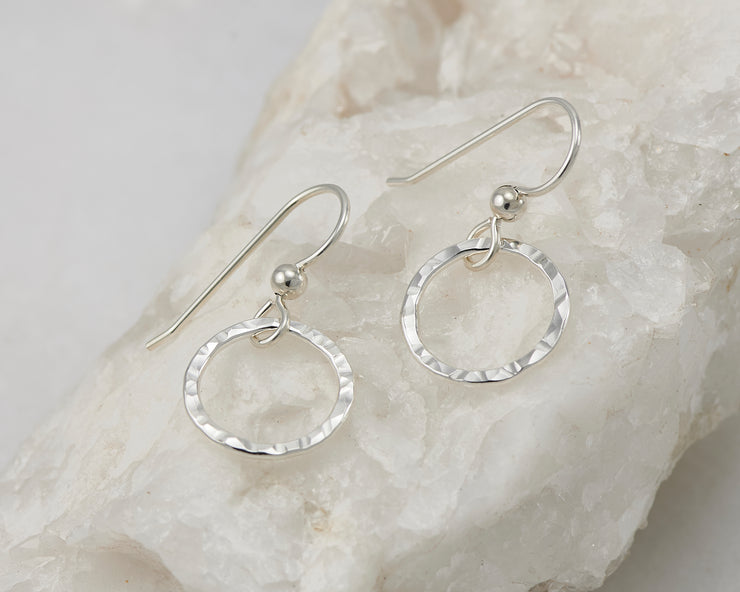 Silver dangle hammered hoop earrings on white rock