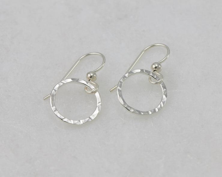 silver hammered hoop earrings on white marble