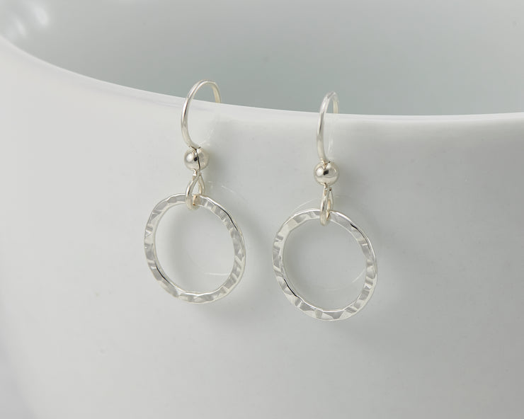 silver hammered hoop earrings on white cup