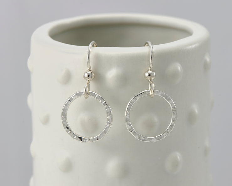 silver hammered hoop earrings on geometric vase