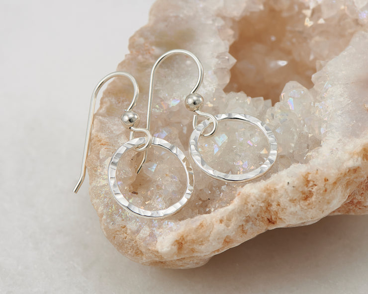 silver hammered hoop earrings on quartz