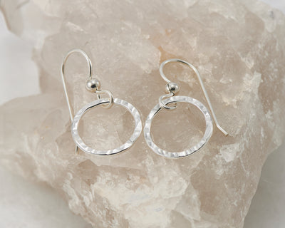 silver thread earrings on white crystal