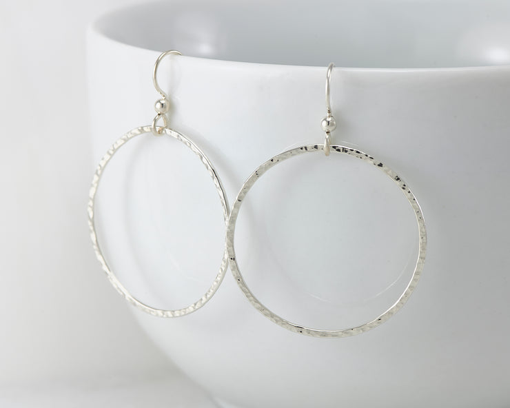 Silver large hammered hoop earrings on white cup