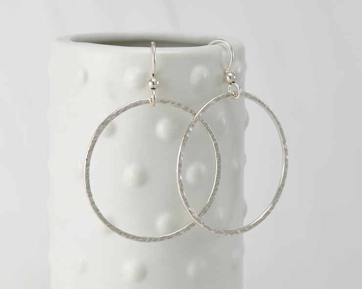 Silver large hammered hoop earrings on dotted vase