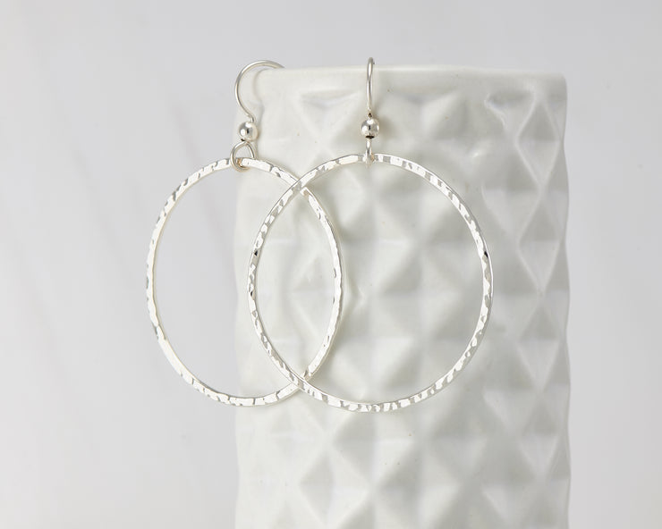 Silver large hammered hoop earrings on geometric vase