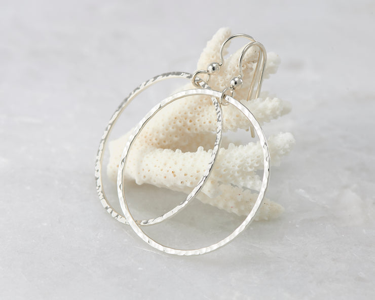 Silver large hammered hoop earrings on coral