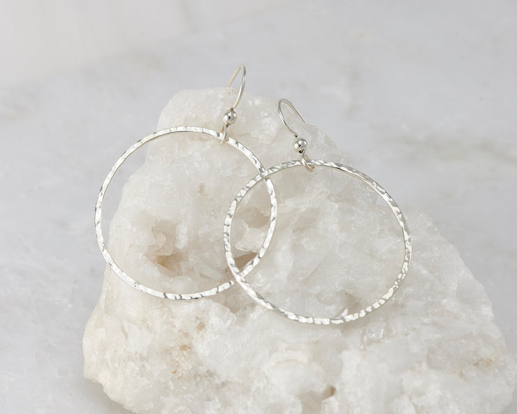Silver large hammered hoop earrings on white rock
