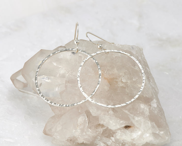 Silver large hammered hoop earrings on crystal rock