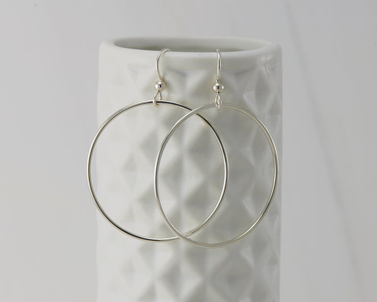 silver large hoop earrings on geometric vase