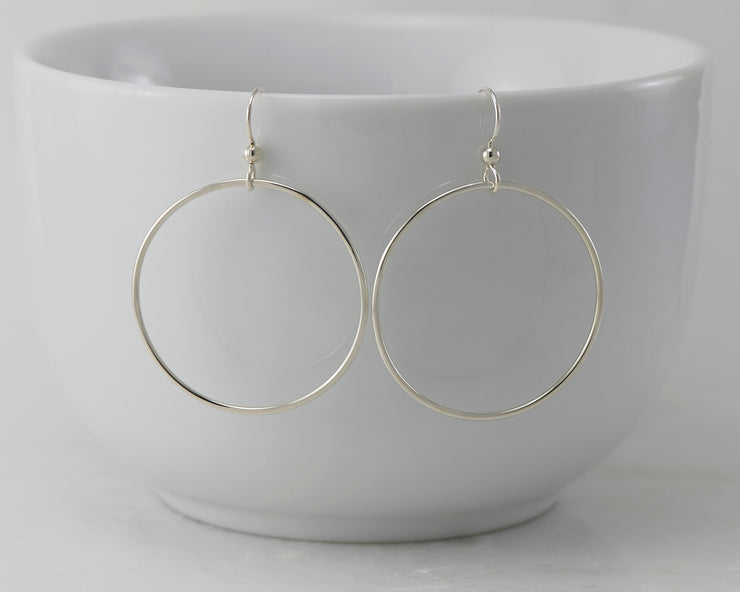 silver large hoop earrings on white cup
