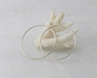 silver large hoop earrings on coral