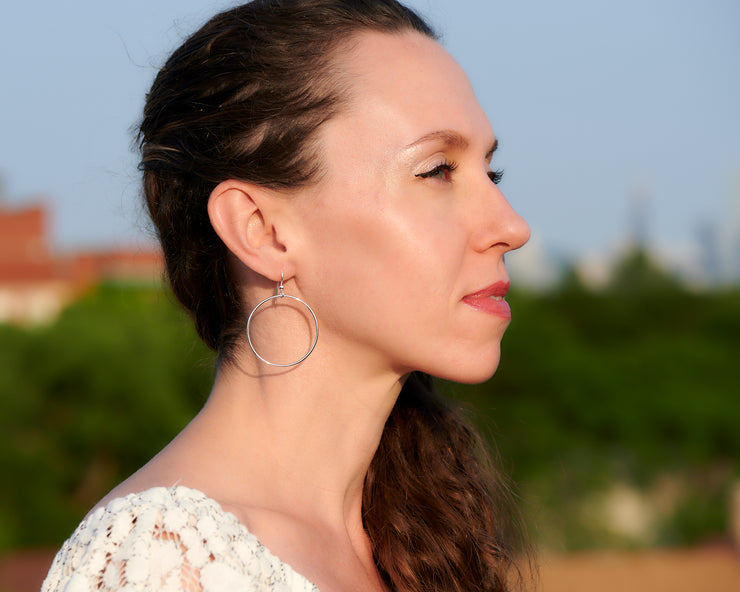 woman wearing silver large hoop earrings