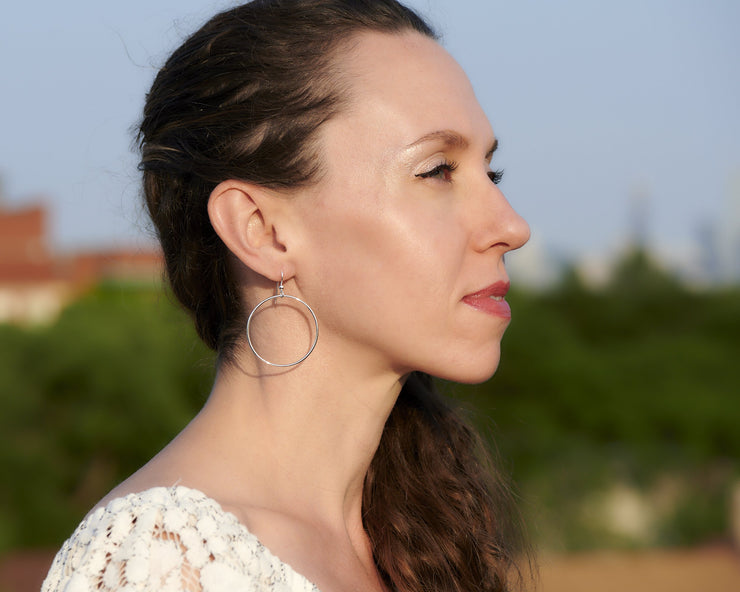 Woman wearing silver large hammered hoop earrings