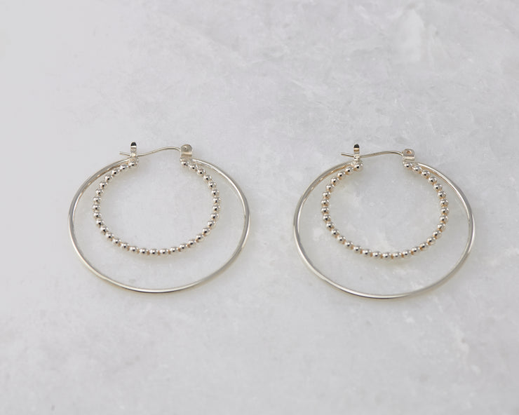 Silver polished latch-back hoop earrings on white marble