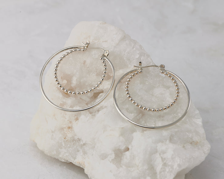Silver latch-back hoop hoop earrings on white rock