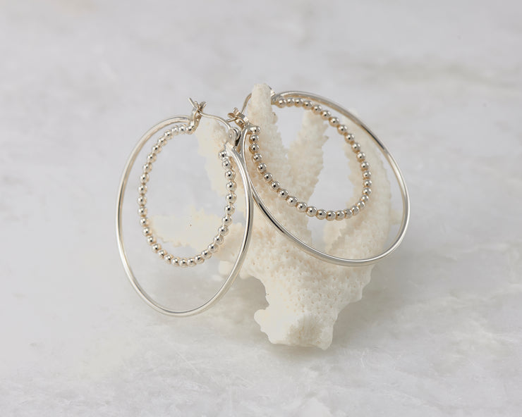 Silver latch-back hoop earrings on coral