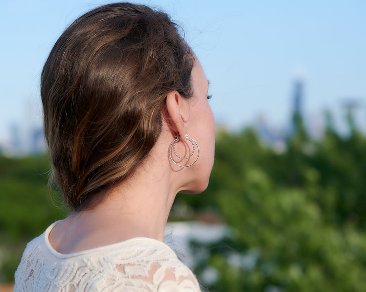 Woman wearing silver hoop latch-back hoop earrings facing away