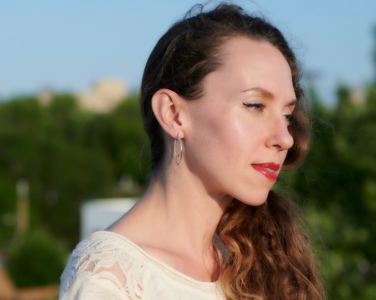 Woman wearing silver hoop latch-back hoop earrings