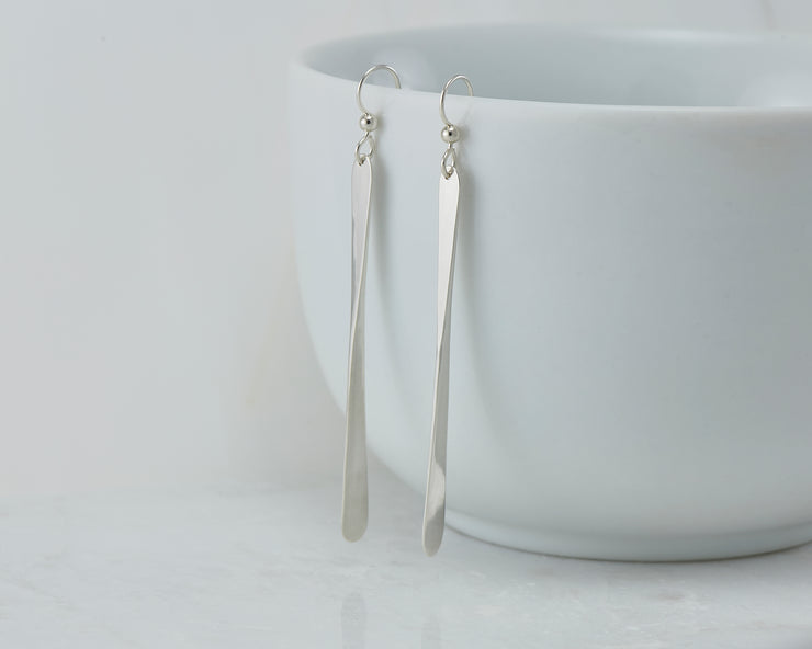 long silver bar earrings on white cup