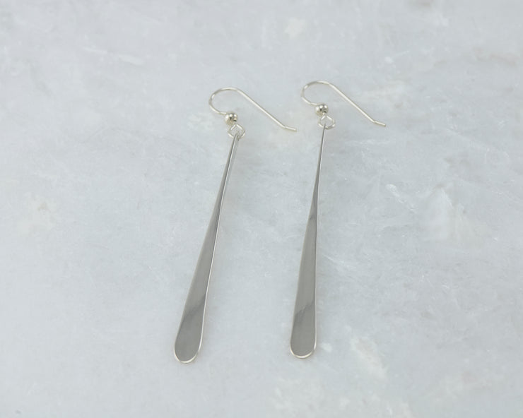 long silver bar earrings on white marble