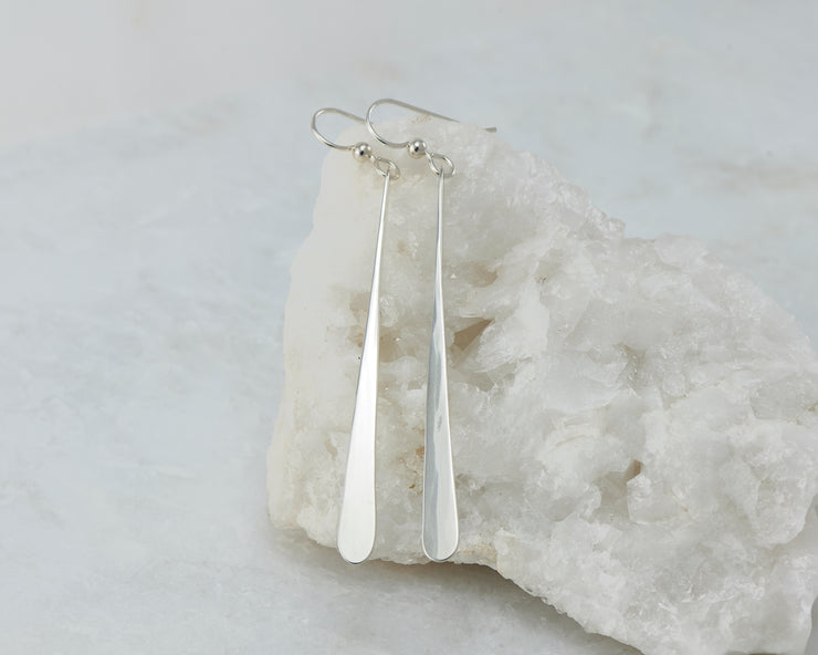 long Silver dangle bar earrings on white rock