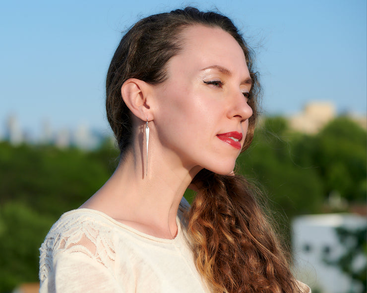 woman wearing long silver bar earrings