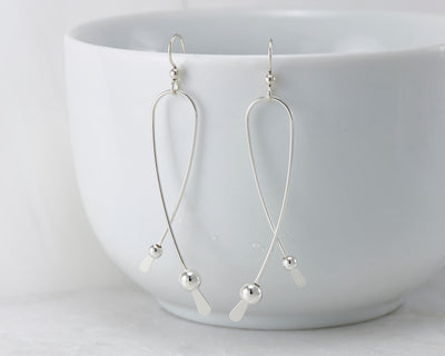 Silver long curved earrings on white cup