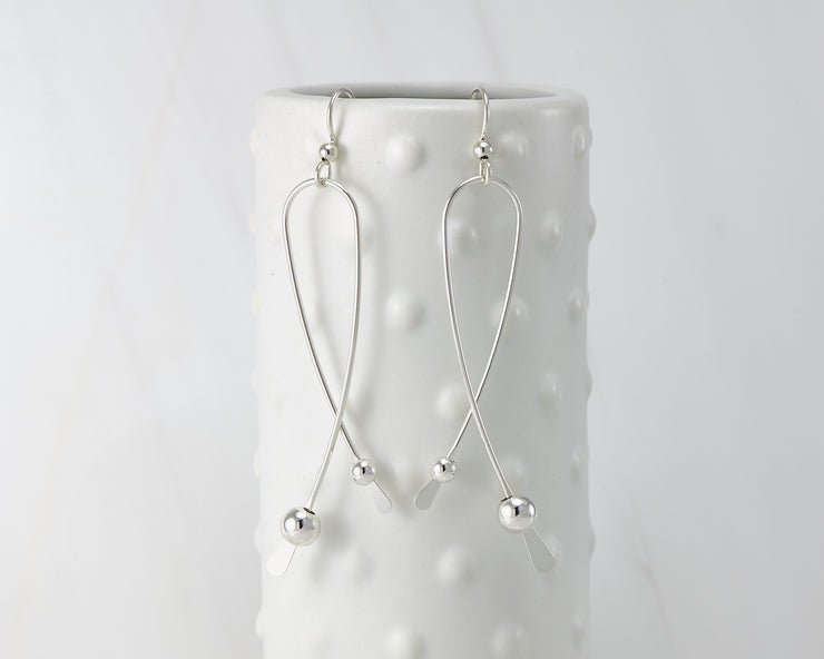 Silver long curved earrings on dotted vase