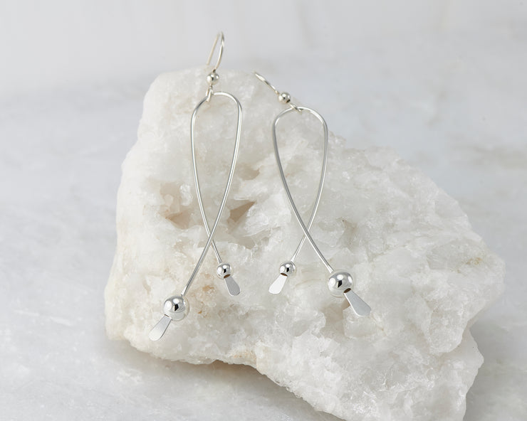 Silver long curved earrings on white rock