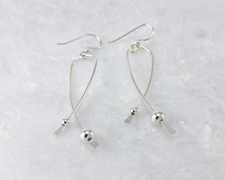 Silver long curved earrings on white marble