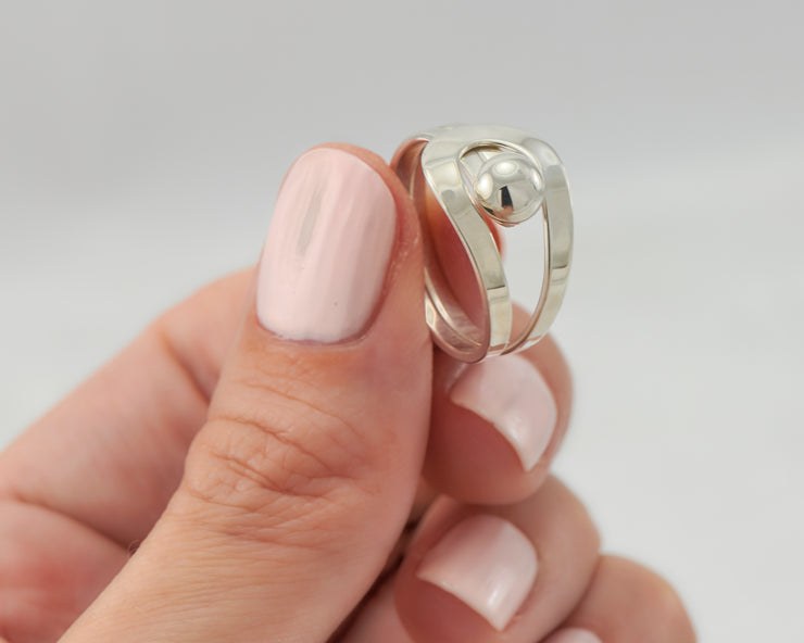 Woman holding silver wrap ring