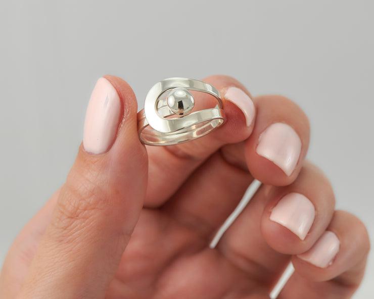 Woman holding modern silver ring