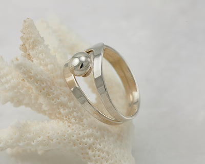 Silver modern ring on coral