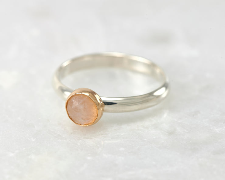 moonstone engagement silver and gold ring on white marble