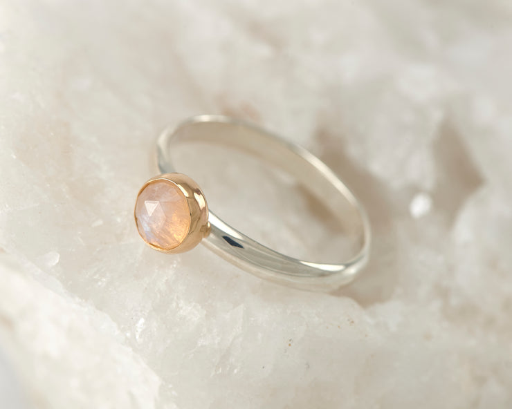 silver and gold moonstone engagement ring on white rock