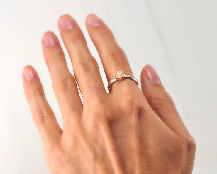 woman wearing moonstone engagement silver and gold ring