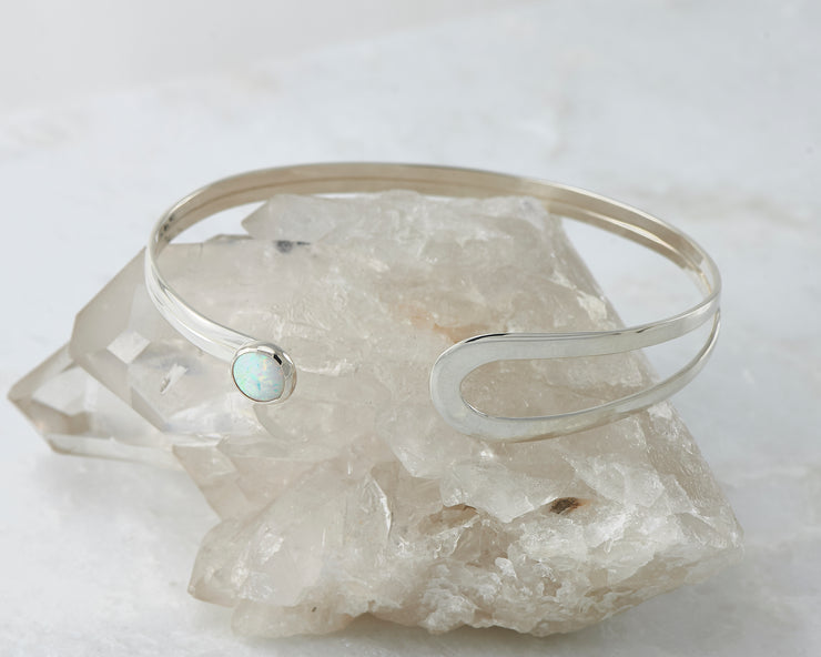 opal latch bracelet shown open on crystal rock