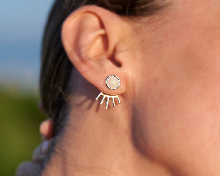 Woman wearing silver stud opal earrings
